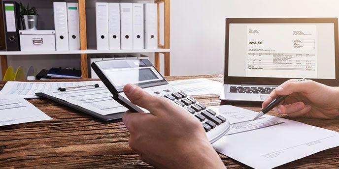 Mann mit Taschenrechner und Kalkulationstabellen, die ein Budget planen