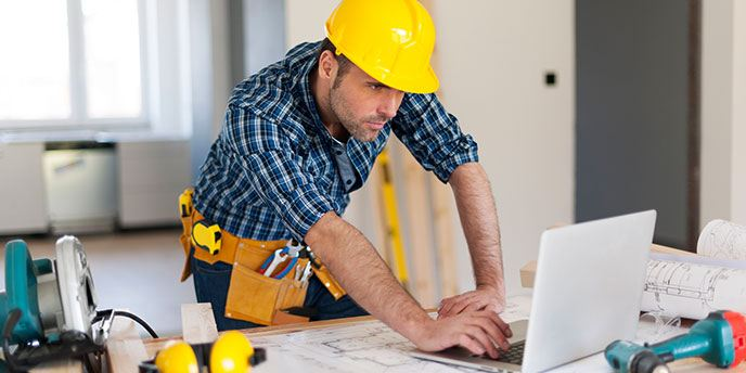 Auftragnehmer-tragender Schutzhelm und Schauen zu Hause der Projektpläne