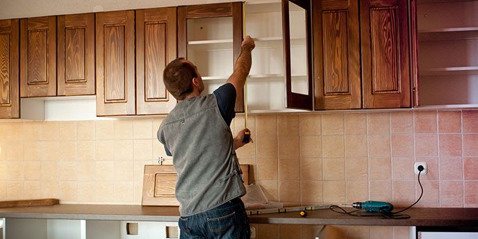 Man Measuring Cabinets in Renovated Kitchen