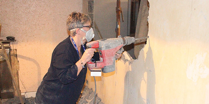 Woman Using Reciprocating Saw to Remove Wall