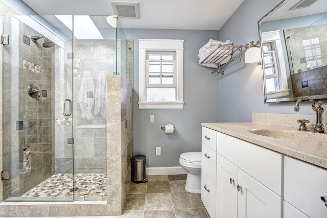 Pale Blue And Beige Bathroom With Tub Converted To A Curbed Walk In Shower.