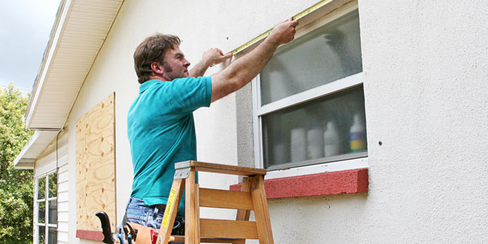 Man Measuring Window for Storm Shutter
