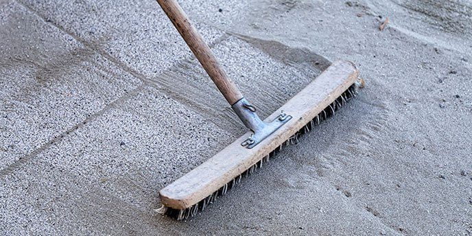 Broom Sweeping Sand Over the Cracks of Patio Paver