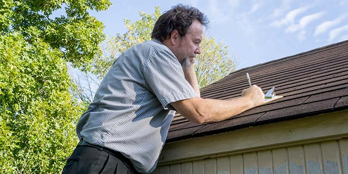 Man With Clipboard Inspecting Roof
