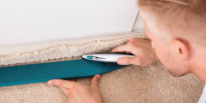 Man Cutting Carpet to Fit During Installation