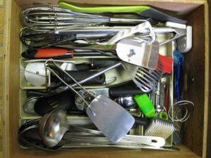 A messy kitchen drawer.