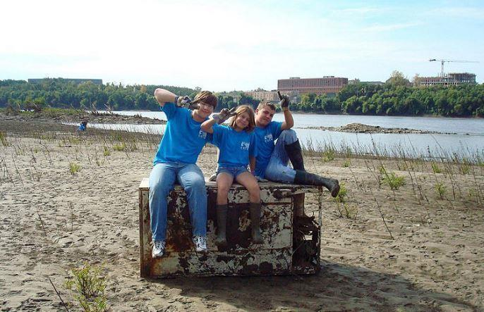 Three child volunteers for a river cleanup event.