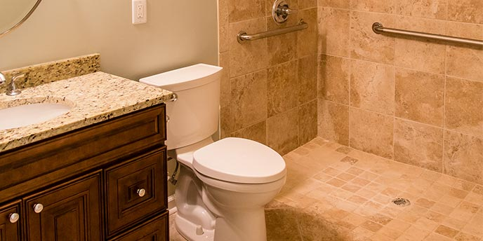 Curbless Shower in Bathroom Next to Toilet and Sink With Marble Countertop and Wood Cabinets