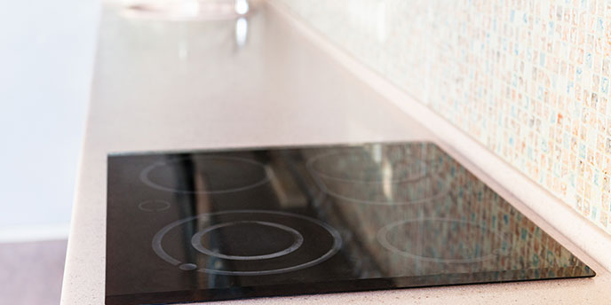 Black Electric Cooktop with Four Burners on Counter