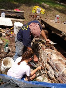 Volunteers engaged in historic preservation of a brick wall.