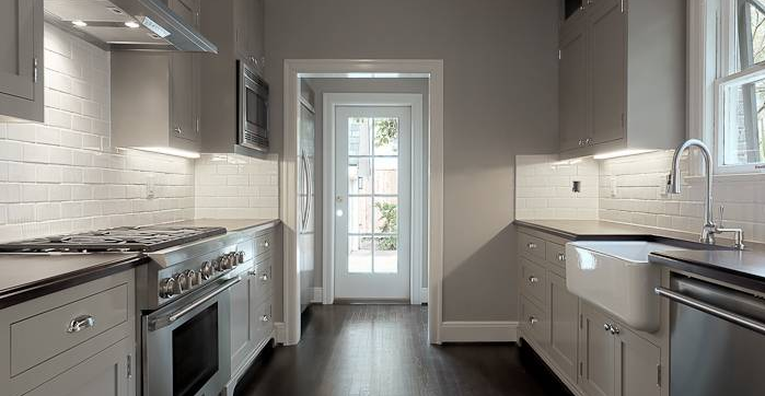 A galley kitchen with light gray walls.