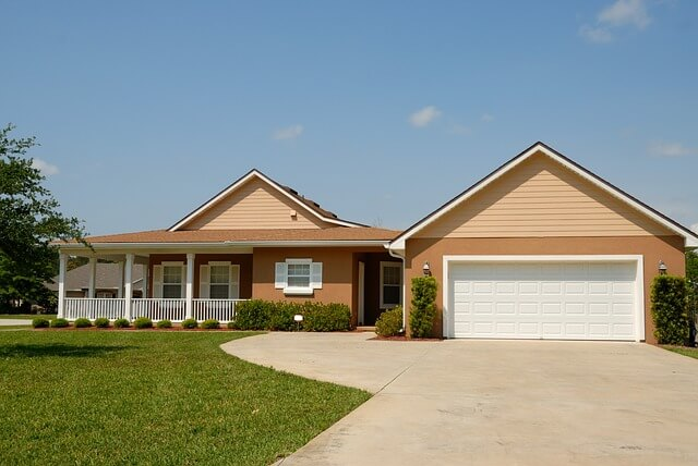 Tan House With a Concrete Driveway