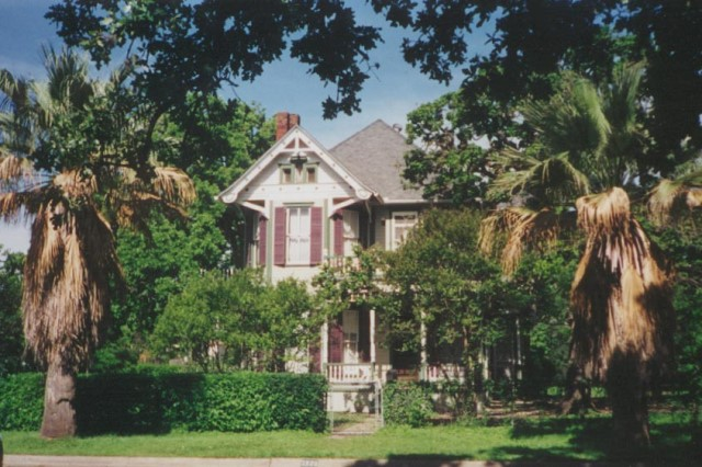 A historic home in Austin hidden by trees.