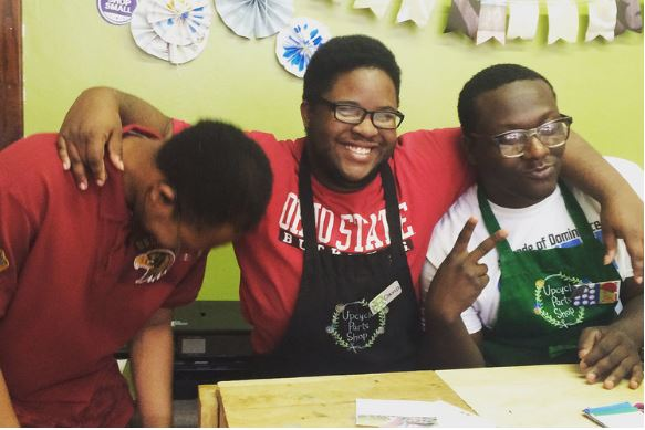 3 smiling young men at an Upcycle Parts Shop event.