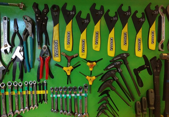 Tools hanging on a green garage wall.