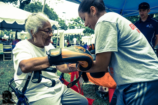 An elderly woman participates in a health activity at the Lincoln Park Music Festival.