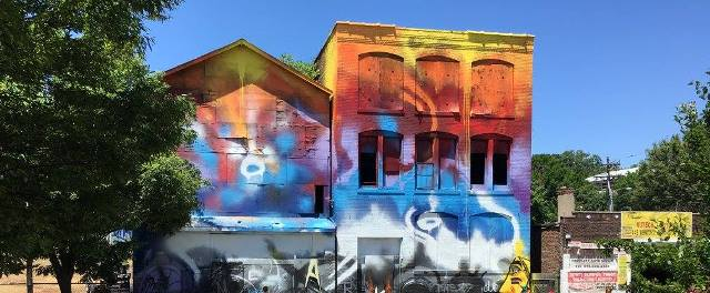 A colorful, abstract mural painted across two buildings.