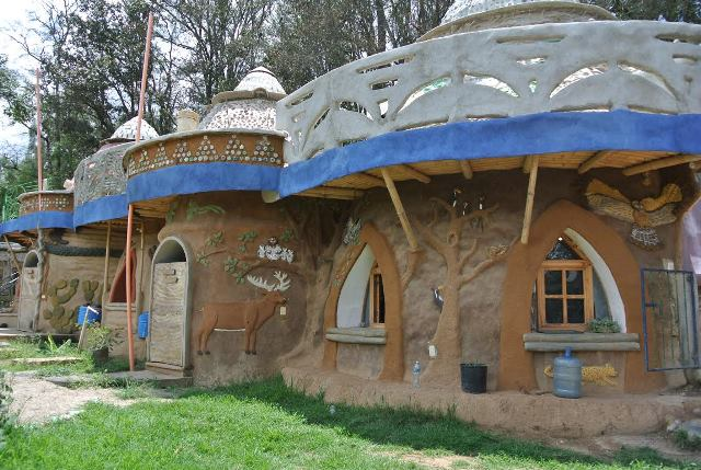 Exterior of sustainable school, formed of connected, conical structures decorated with local cultural motifs.