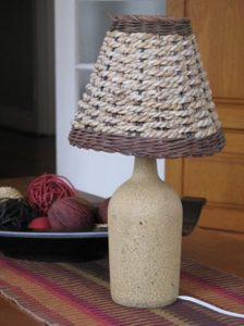 Reusing a glass bottle by turning it into a lamp with a taupe finish and basket-style shade.