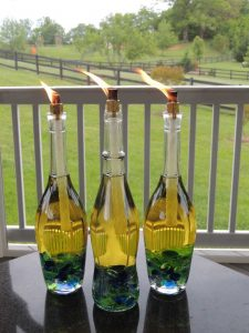 Wine Bottles Turned Into Oil Lamps, With Lit Wicks.