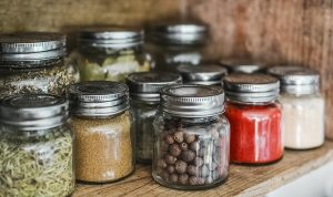 Glass Jars Filled With Spices Inside a Cupboard.