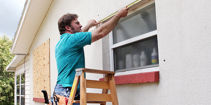 Image of a Man Installing Plywood Hurricane Shutters