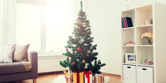 Artificial Christmas Tree in a Bright Living Room Next to Couch and Shelves
