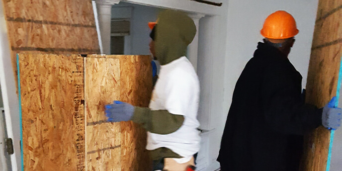 Two Men Moving Plywood Panels