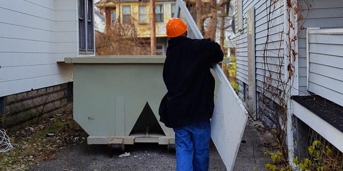 Man Throwing Trash in Dumpster