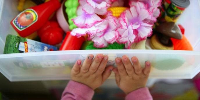 Child's Hands Closing Toy Bin Organizer Filled With Children's Toys