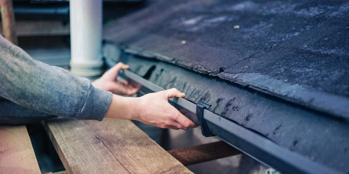 Person Repairing a Gutter