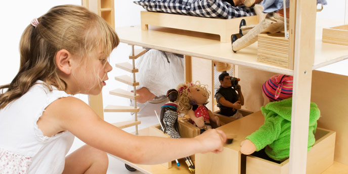 Young Girl Playing with Dolls In Wooden Doll House
