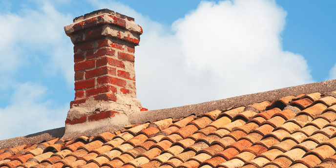 Brick Chimney on Terracotta Roof in Front of Partly Cloudy Skies