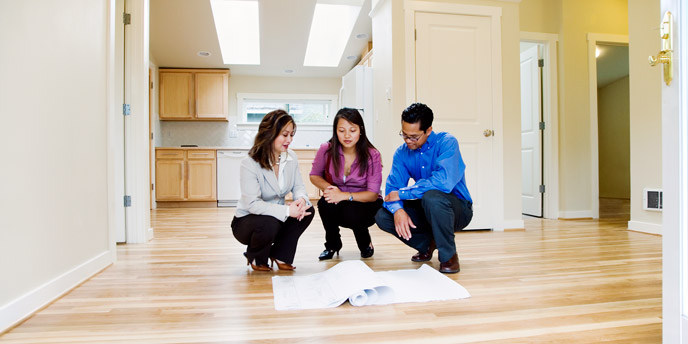 Homeowners Crouched on Kitchen Floor Looking at Plans for a DIY Kitchen Island