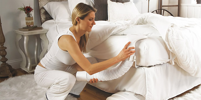 Woman Using a BedJet Bed Cooling System to Keep Her Bed Cool Without AC