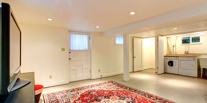 Semi-Finished Basement Media Room with Laundry Machines in Back