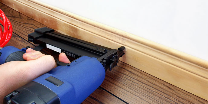 Carpenter Using Nail Gun on Baseboard