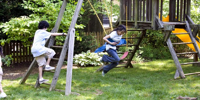 Children Playing on Wooden Swingset