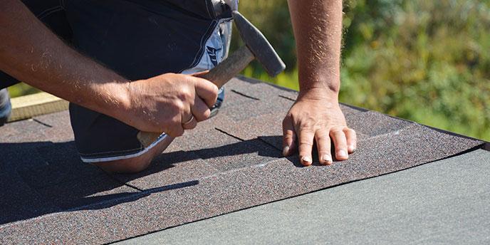 Worker Installing Roof Shingles