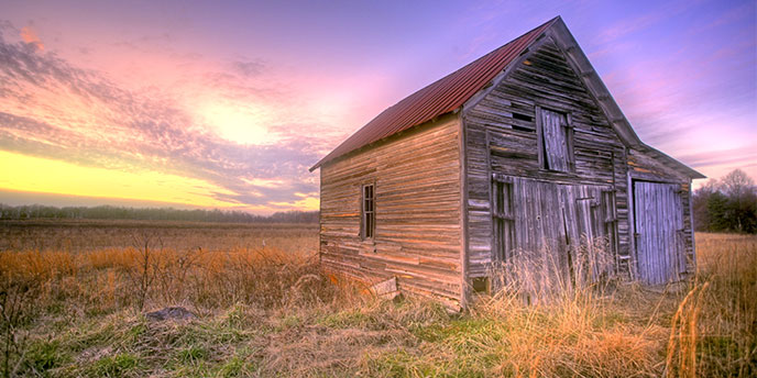 Old Barn in a Field at Sunrise