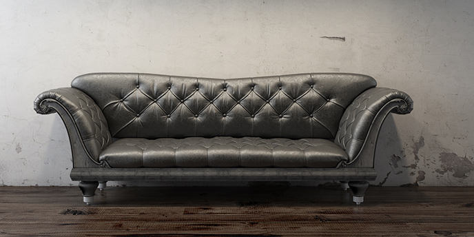 Black Couch In Front Of Dingy Grey Wall