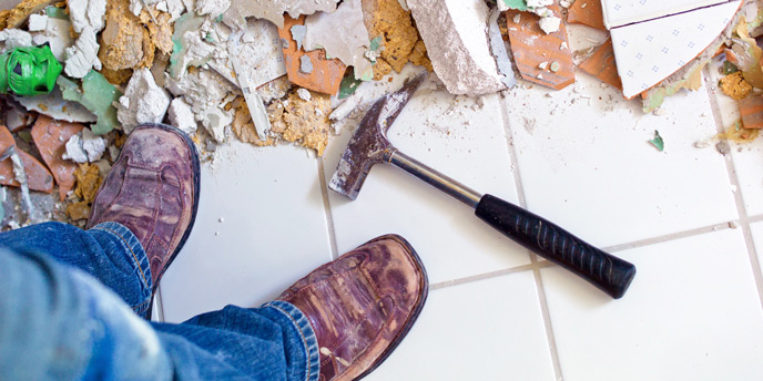 Man Demolishing a Bathroom Floor