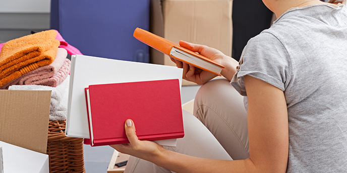 Woman Packing Red and Orange Books for a Move