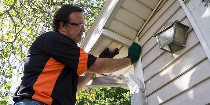 Man on Ladder Repairing Vinyl Siding
