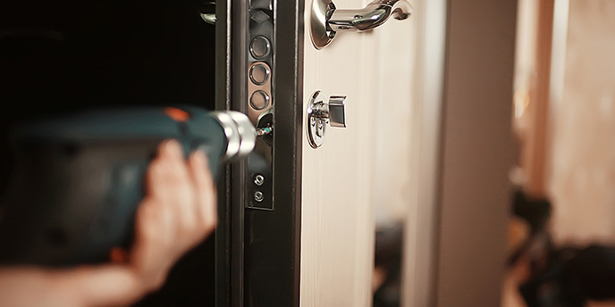 Person Using a Drill to Change Locks Before Moving In