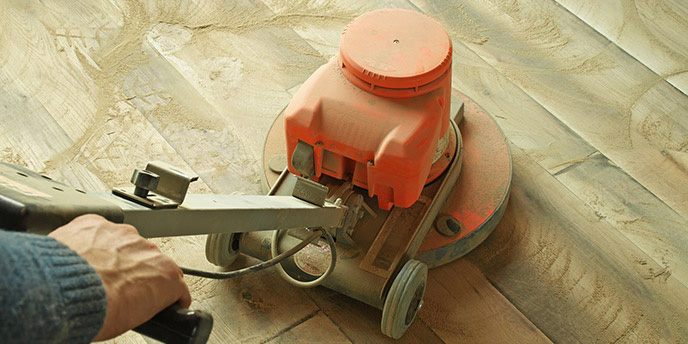 Man Using Sander to Refinish Hardwood Floors Before Moving In