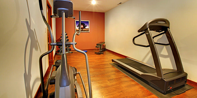 Elliptical and Treadmill Machines on Hardwood Floor in Basement Home Gym.