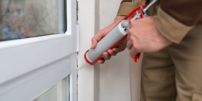 Man Using Caulk Gun to Seal Windows.
