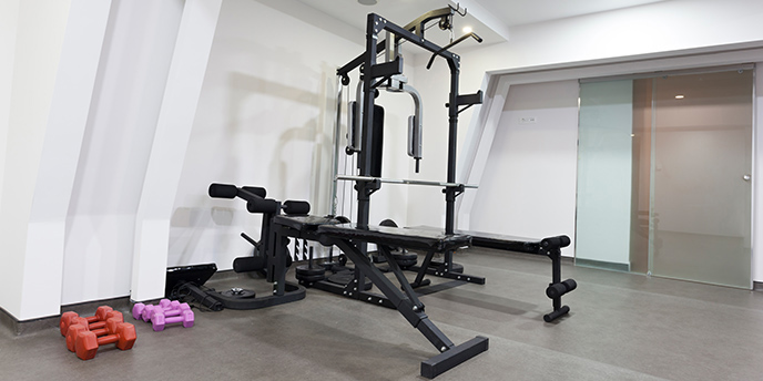 Weight Benches and Lifting Machines Near Dumbbells in Basement Home Gym.