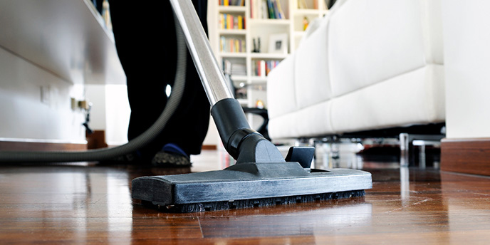 Person Vacuuming Wood Living Room Floor.